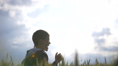 Boy with phone rejoices in the field, boy is very happy on a background of sky Stock Footage