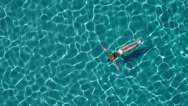 Aerial - Beautiful young woman with toned body swimming underwater Stock Footage