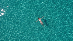 Aerial - Raising above young woman floating in crystal clear waters Stock Footage