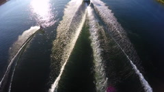 Aerial birds-eye drone view of a man wakeboarding behind a boat. Stock Footage