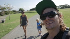 Selfy of sporty parents and cute child with skateboard smiling and waving hands Stock Footage