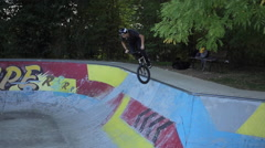 A young man rides a BMX bicycle in a concrete skate park. Stock Footage