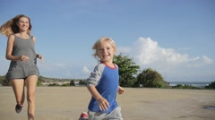 Steadicam shot of child playing, laughing, running to take hand in park Stock Footage