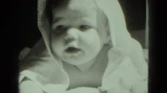 1947: baby with towel in sun after bath showing hand of caregiver Stock Footage