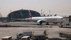 Pushback of a boeing 777 emirates plane at dubai Stock Footage