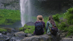 Hikers Sit On Rock And Enjoy Waterfall And Surroundings, They Point To Things Stock Footage