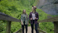 Hikers Cross A Bridge And Look Around At The Beautiful Scenery Stock Footage