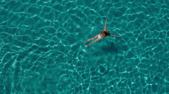 Aerial - Woman in white bikini swimming underwater in crystal clear water Stock Footage