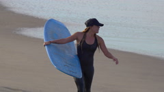 A young woman in a wetsuit walking with her longboard surfboard. Stock Footage