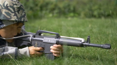 Teen in camoflauge playing war shoots a toy gun Stock Footage
