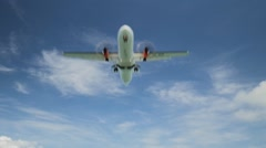 Airplane landing on island Bali airport under blue sea with waves on the horizon Stock Footage