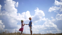 Boy Giving a Flower to Fashionable Girl on a Background of Clouds. Love Concept Stock Footage
