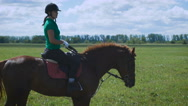 Young woman riding a horse on the green field Stock Footage