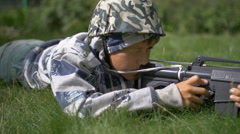 Child playing war shoots a toy gun Stock Footage