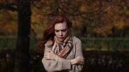 Beautiful woman freezing in autumn park, cold autumn Stock Footage