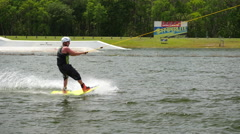 A man rides his wakeboard at a cable park. Stock Footage
