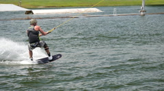 A man jumping his wakeboard off a ramp at a cable park. Stock Footage