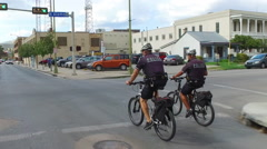 Two Police Officers on Bicycles Patrol the Streets of San Antonio Stock Footage