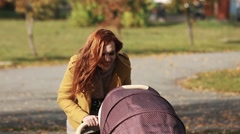 A young mother with a baby carriage walking in a park Stock Footage