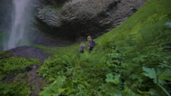 Wide Shot Of Hikers Reaching The End Of A Trail, Enjoying A Waterfall Stock Footage