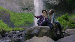 Friends Sit And Use Gopro To Take Selfies Together, With Waterfall In Background Stock Footage