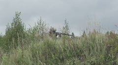 War in the grass attacking enemy. Soldier shoots in a field Stock Footage