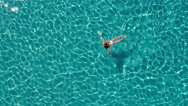 Aerial - Beautiful young woman in bikini enjoys swimming in crystal clear waters Stock Footage