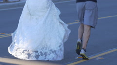 A couple running in a wedding costume in a 10K race. Stock Footage