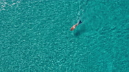 Aerial - Flyover young woman enjoying snorkeling in crystal clear waters Stock Footage