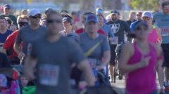 A crowd of people running in a 10K baby stroller race. Stock Footage