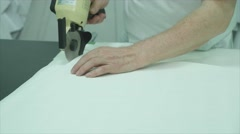 Woman cutting a piece of cloth at table in fashion studio Stock Footage