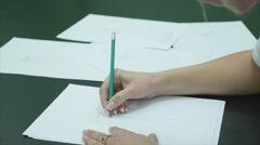 Human hands with pencil draw dress on paper on white table background Stock Footage