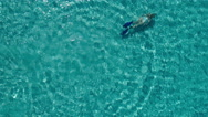 Aerial - Top view of young woman snorkeling underwater in crystal clear waters Stock Footage