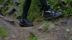 Camera Pans And Follows Woman Hiker's Feet As She Walks Along Rocky Trail Stock Footage