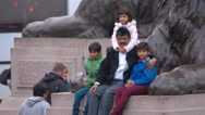 People posing for photos at the lions of Trafalgar Square in London Stock Footage