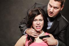Scene of violence with firearm between men and women. Stock Photos