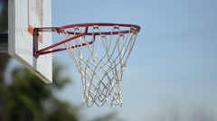 Extreme closeup of a man slam dunking a basketball on a playground court. Stock Footage