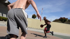 Men playing two-on-two pick up basketball on a playground court. Stock Footage