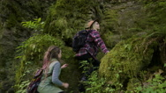 Women Hikers Climb Up Trail Through Rain Forest, Point Out Something In Distance Stock Footage