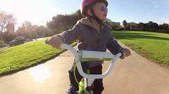 POV of a boy riding a bicycle at a park. Stock Footage