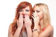 Society gossip - two happy young girlfriends talking white background Stock Photos