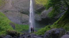 Hikers Climb On Rock Beneath Huge Waterfall, Woman Raises Arms And Hugs Friend Stock Footage