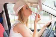 Woman applying makeup while driving her car Stock Photos