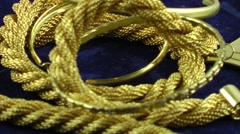 Gold jewellery rotating on dark blue background Stock Footage