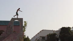 A young man doing a silly dance on top of a wall. Stock Footage