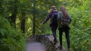 Carefree Hikers Balance On Rock Wall Beside Hiking Path Stock Footage