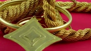 Gold jewellery rotating on red background Stock Footage