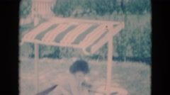 1949: little girl playing in fancy sandbox with shade structure Stock Footage