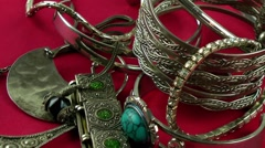 Silver jewellery rotating on red background Stock Footage