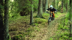 A young man riding a mountain bike on a trail through the woods. Stock Footage